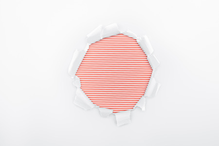 ripped hole in textured white paper on red striped background Stock Photo