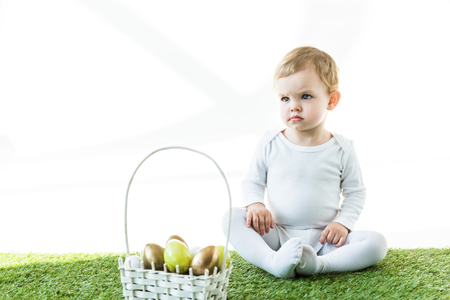 cute baby sitting on green grass near straw basket with colorful Eastern eggs isolated on white