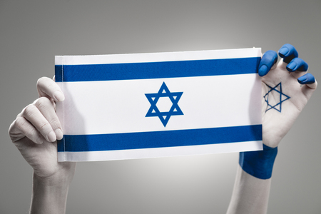 cropped view of female hands holding national flag of israel on grey Stock Photo