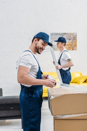 handsome mover in uniform wrapping cardboard box with stretch film in apartment