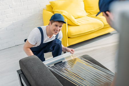 smiling mover wrapping couch with roll of stretch film in apartment Stockfoto