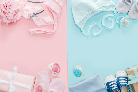 top view of pacifiers, gifts, hat, booties, bonnets, sneakers, socks, bouquet on pink and blue background Stockfoto