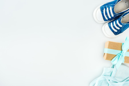 top view of blue sneakers, gift box and bonnet on white background with copy space