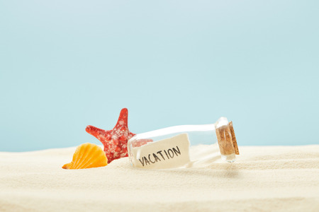 glass bottle with vacation lettering on paper near seashell and starfish isolated on blue Zdjęcie Seryjne