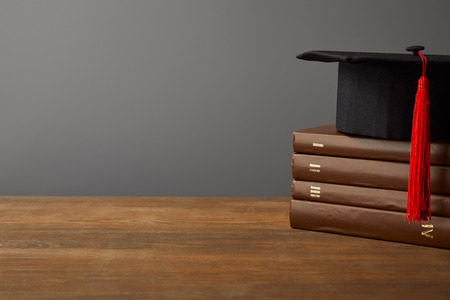 Brown books and academic cap on wooden surface isolated on grey