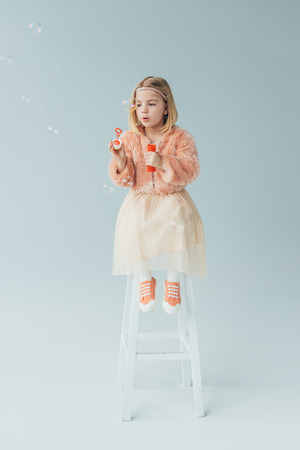 kid in faux fur coat and skirt sitting on highchair and blowing soap bubbles Stock Photo