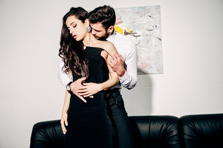 bearded man kissing and touching brunette woman in black dress 免版税图像