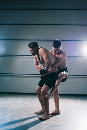 muscular mma fighter clinching sportive shirtless opponent