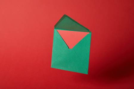 bright,and green envelope with card on red background with copy space