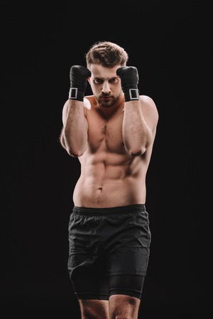 muscular strong shirtless mma fighter in stance isolated on black