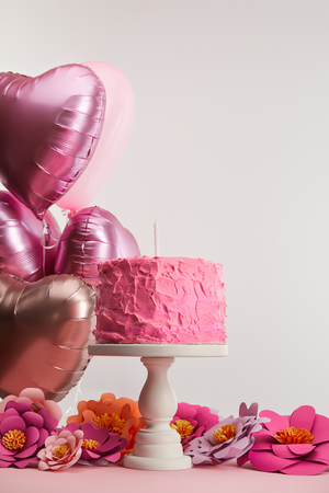 pink birthday cake with candle on cake stand near paper flowers and heart-shaped air balloons on grey