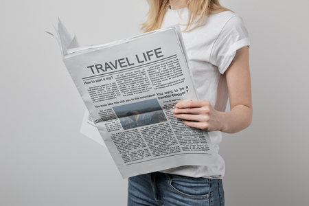 cropped view of woman reading travel newspapers isolated on grey