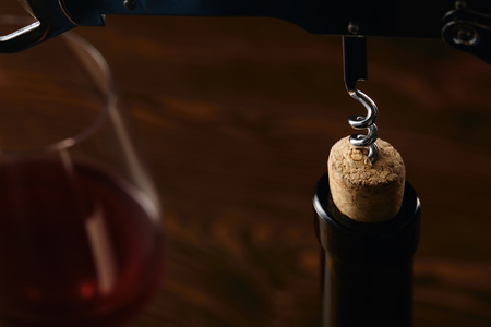 Bottle with wooden cork and steel corkscrew on brown