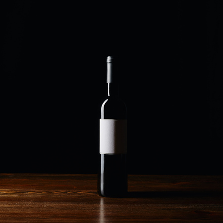 Wine bottle with blank label on wooden surface isolated on black