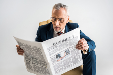 mature businessman in glasses and suit reading business newspaper isolated on grey