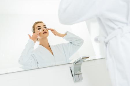 selective focus of woman in white bathrobe applying face cream in bathroom Stok Fotoğraf