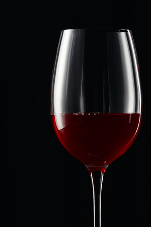 Glass with burgundy red wine isolated on black Stok Fotoğraf