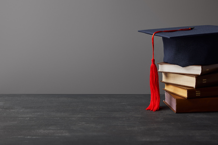 Brown books and academic cap with red tassel isolated on grey 写真素材