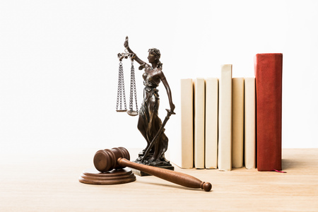 metal figurine with scales of justice, brown gavel and books on wooden table isolated on white