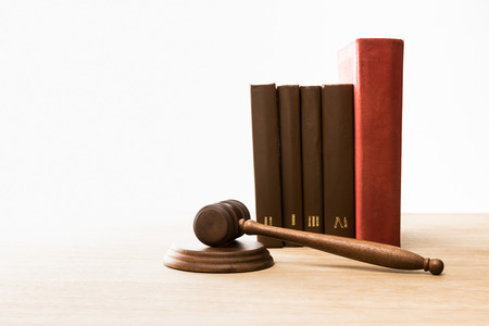 wooden gavel and row of books on wooden table