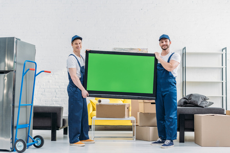 two movers in uniform looking at camera while transporting tv with green screen in apartment