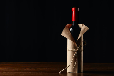 Wine bottle in paper wrapper on wooden surface isolated on black 版權商用圖片