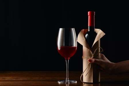 Partial view of woman holding wine bottle in paper wrapper Stockfoto