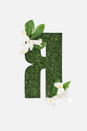 cut out cyrillic letter with green grass on background, leaves and white flowers isolated on white