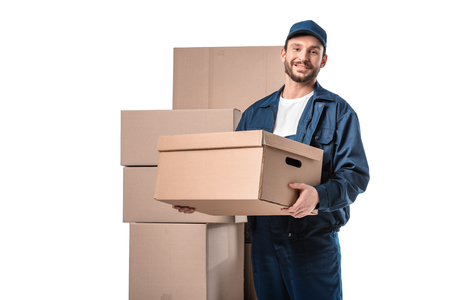 smiling handsome mover in uniform carrying cardboard box and looking at camera isolated on white with copy space