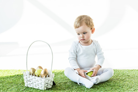 adorable child sitting on green grass near yellow and golden Easter eggs isolated on white Standard-Bild - 119792921