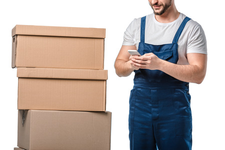 cropped view of mover with cardboard boxes using smartphone isolated on white Stockfoto