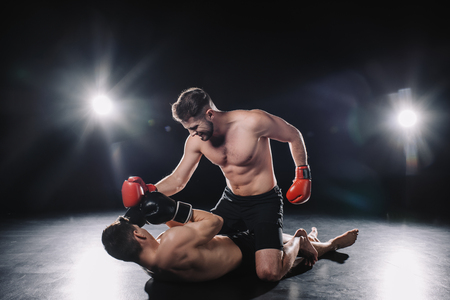 strong mma fighter in boxing gloves punching opponent while sportsman lying on floor Stock Photo