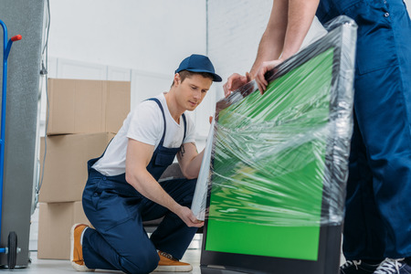two movers in uniform using roll of stretch film while wrapping tv with green screen in apartment