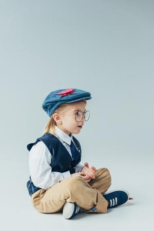 surprised kid sitting with crossed legs on floor and looking away