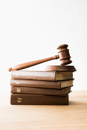 gavel on pile of brown books on wooden table isolated on white Imagens