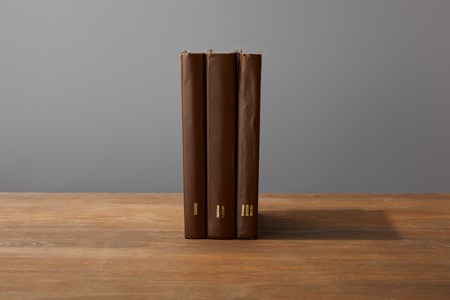 Brown books on textured wooden surface isolated on grey