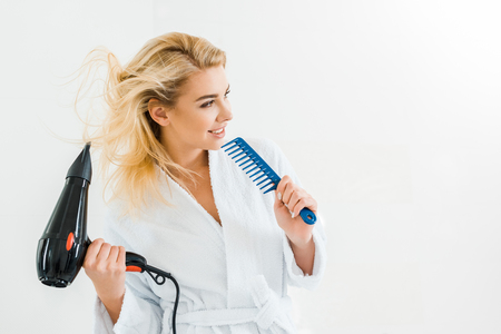 beautiful and smiling woman in white bathrobe holding hairdryer and comb