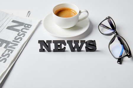 news lettering near cup of coffee, glasses and business newspaper on white