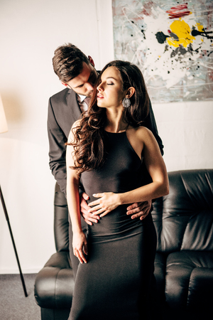 handsome man in suit kissing beautiful woman in black dress