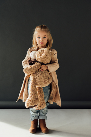run shoes 2020 distinctive style surprised and cute child in trench coat and jeans holding teddy..