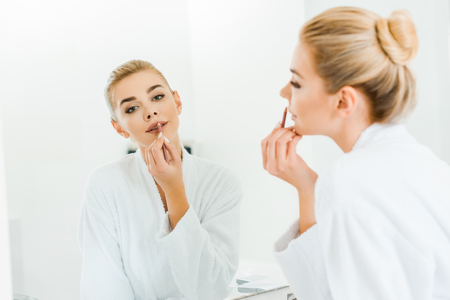 selective focus of beautiful and blonde woman in white bathrobe applying lip liner and looking at mirror