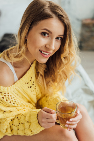 beautiful smiling young woman sitting on bed, looking at camera and holding cup of tea