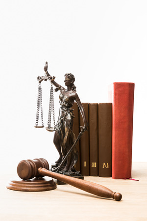 figurine with scales of justice, gavel and books on wooden table isolated on white Stock Photo