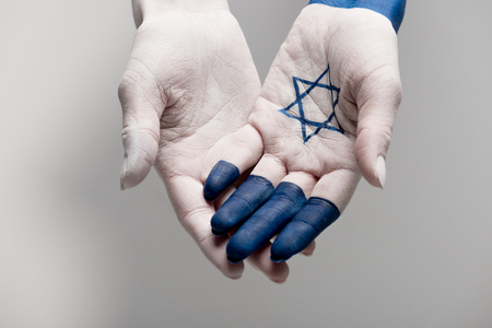 cropped view of hands with blue star of david on grey Stock Photo
