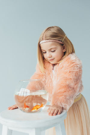 adorable kid in faux fur coat and skirt looking at fishbowl on stool isolated on grey