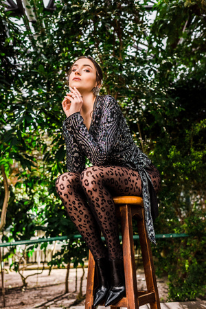 Low angle view of sexy pensive woman in black pantyhose sitting on chair in orangery