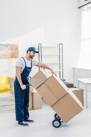 mover in uniform transporting cardboard boxes on hand truck in apartment with copy space