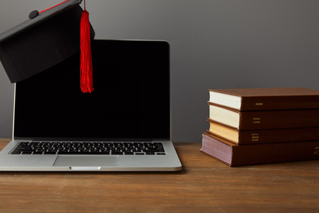 Laptop with blank screen, books and academic cap with red tassel on wooden surface isolated on grey