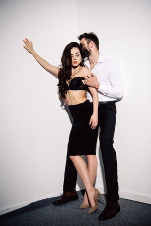 bearded man undressing beautiful woman in black lace bra near white wall