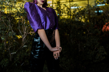 Partial view of woman in purple blouse and leather pants posing in orangery